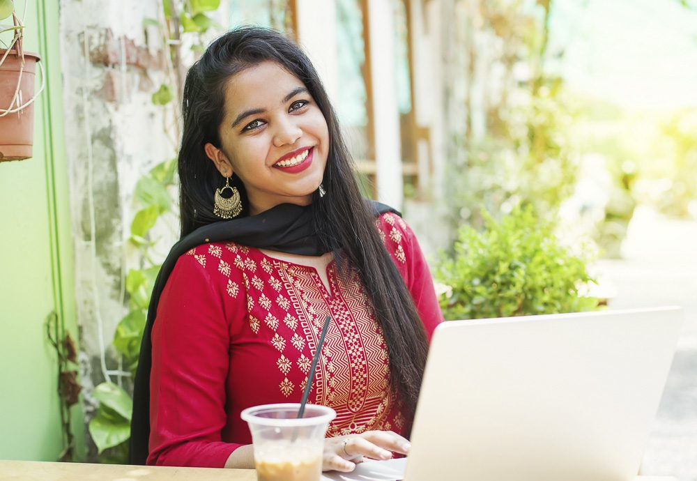 Indian woman with laptop in a cafe