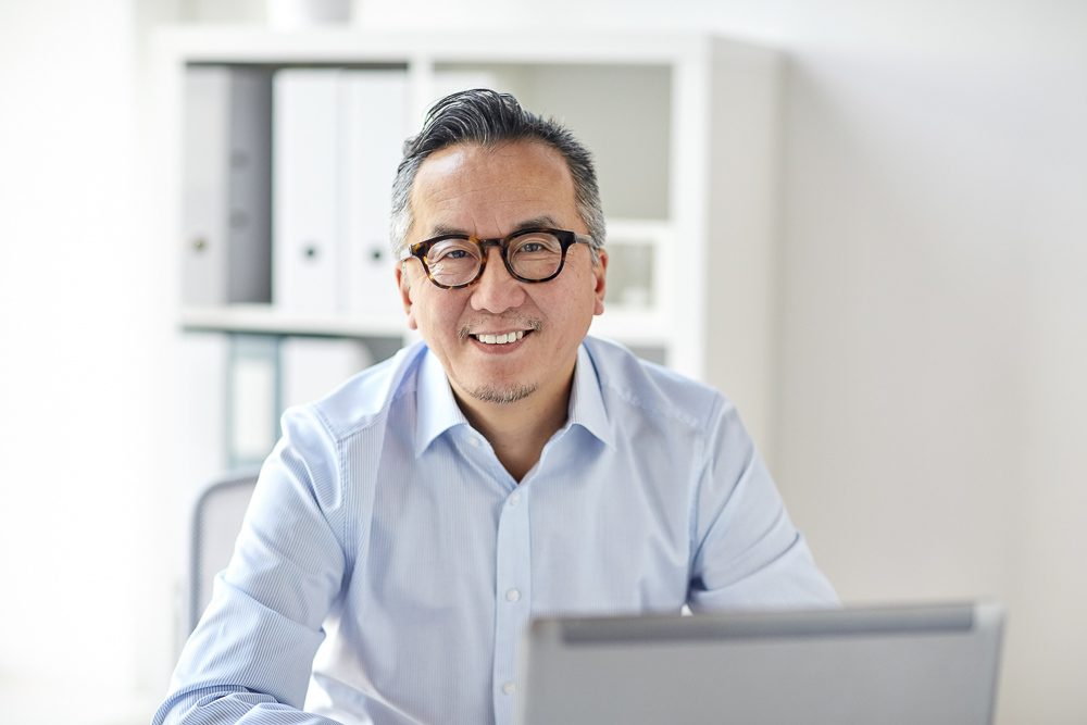 happy businessman in eyeglasses with laptop office