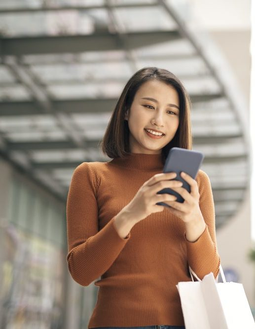 Portrait of elegant young Asian woman holding shopping bags and using smartphone on the go while leaving mall