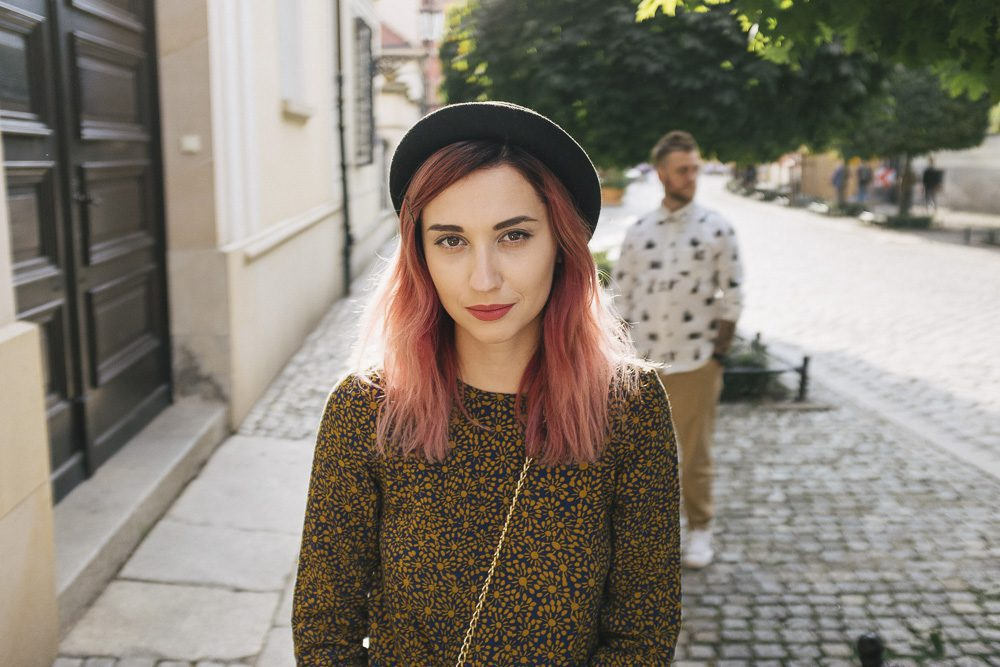 beautiful stylish girl with pink hair looking at camera, boyfrie