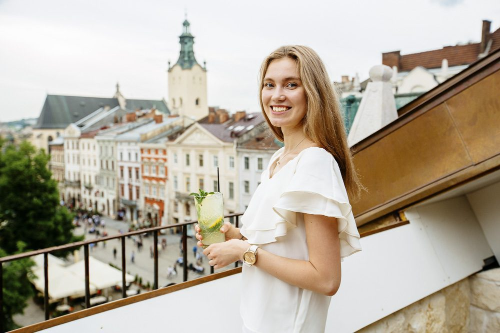 Happy blond smiling woman holding a glass of some drink while enjoying the european city view. Relaxing, tourism and resting concept.