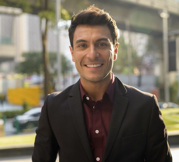 Face of happy young handsome Hispanic businessman smiling in the city
