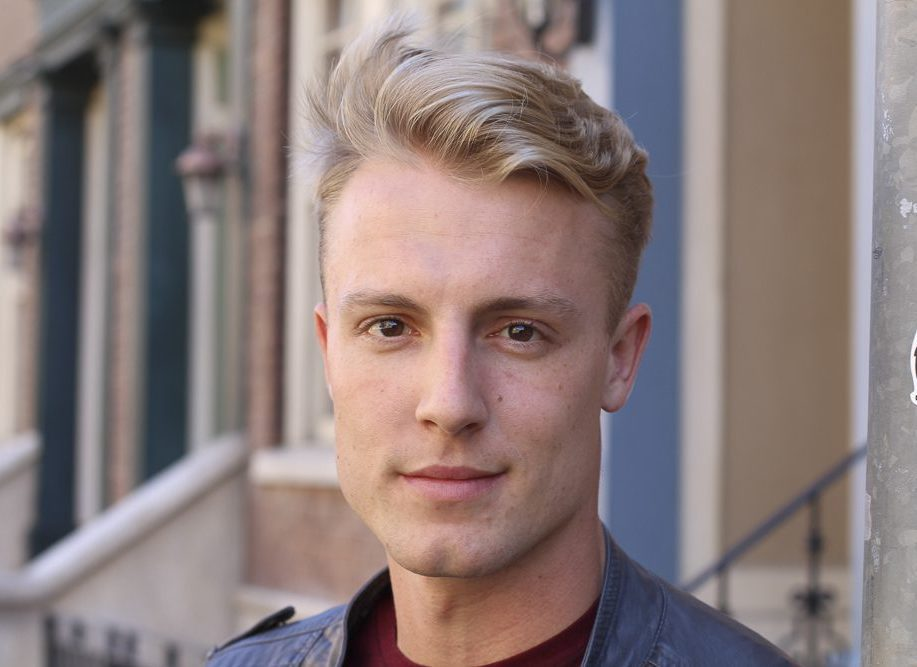 Close portrait of handsome adult blonde man, with blured urban c